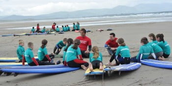 kids taking a surf lesson at inch and banna beach county kerry