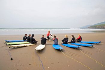 prepping to enter the water for a surf lesson at inch beach in county kerry