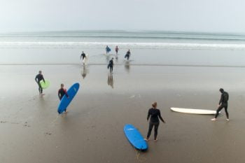 about the enter the water for a surf lesson at inch beach in county kerry